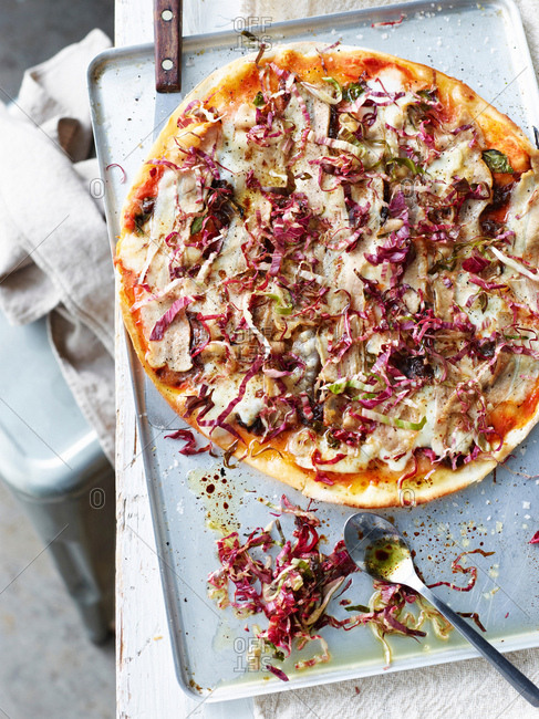 Pork belly and radicchio pizza on baking tray, overhead view