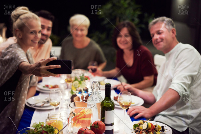 Group of people sitting at table, enjoying meal, young woman taking selfie of group using smartphone