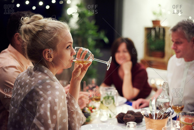 Group of people sitting at table, enjoying meal, young woman drinking from wine glass