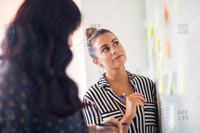Young businesswomen looking at whiteboard adhesive notes