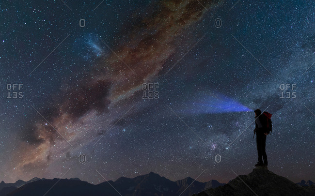 Silhouette of climber on mountain peak looking away at starry night sky, Chamonix, Mont Blanc, Rhone Alpes, France, Europe