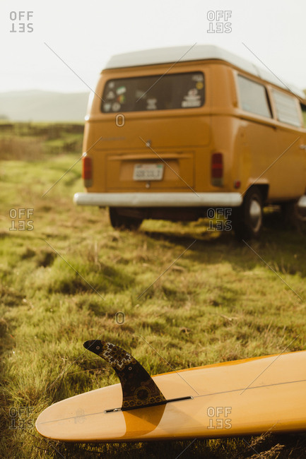Yellow surfboard and vintage recreational van on roadside, Exeter, California, USA