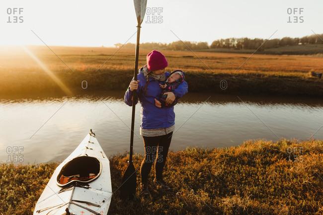 Woman kayaker on riverbank carrying baby daughter at sunset, Morro Bay, California, USA