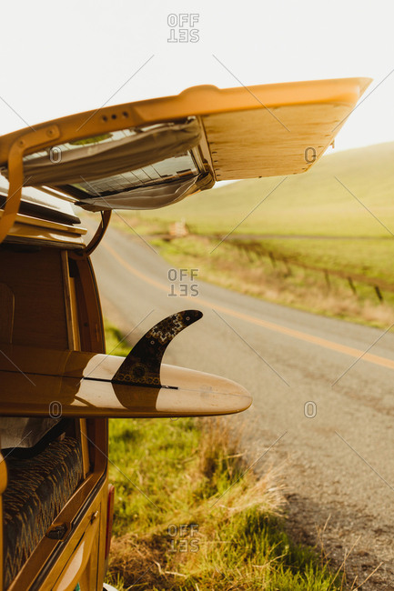 Yellow surfboard in vintage recreational vehicle boot on roadside, Exeter, California, USA
