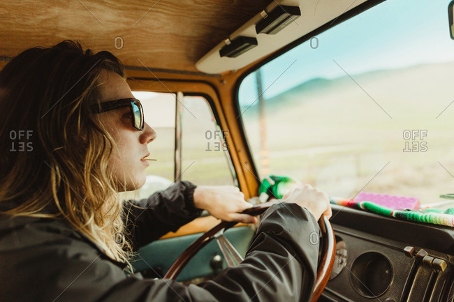 Long haired young man in shades driving vintage vehicle