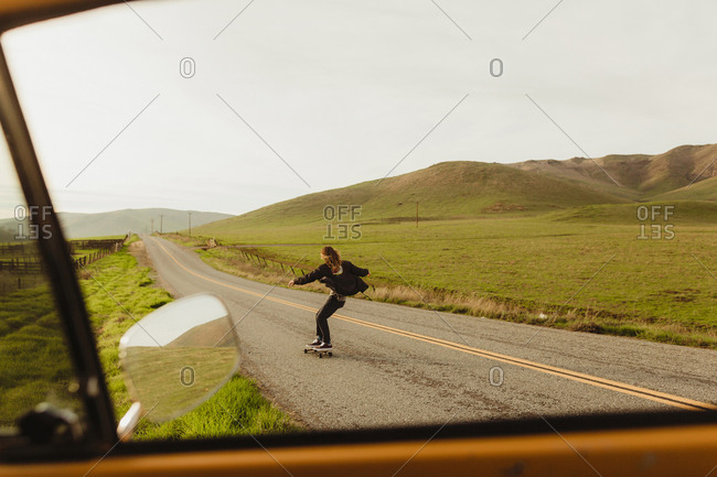 Car window view of young male skateboarder skateboarding along rural road, Exeter, California, USA