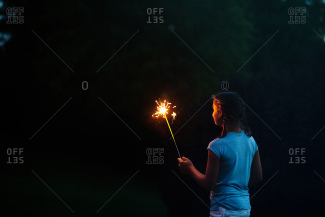 Girl gazing at sparkler in garden at night on independence day, USA