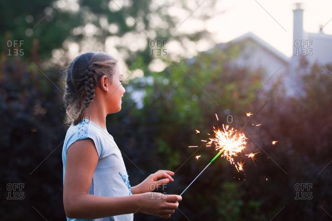 Girl holding sparkler in garden at dusk on independence day, USA