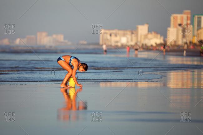 Girl on beach picking up seashells, North Myrtle Beach, South Carolina, United States, North America