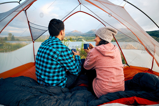 Couple sitting in tent, drinking hot drinks, looking at view