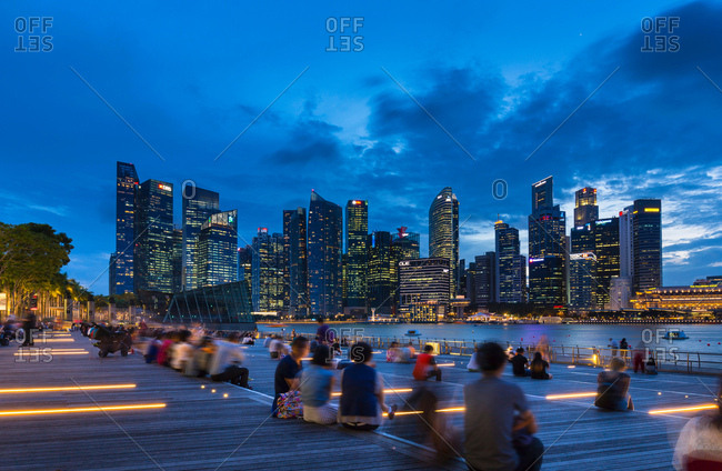 October 23, 2017: Tourists looking at city skyline from waterfront at dusk, Singapore, South East Asia