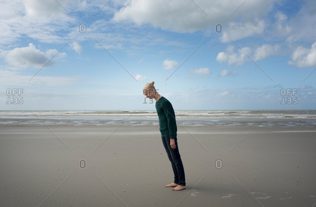 Boy standing on beach, leaning forward in the stormy wind, Gravelines, Nord-Pas-de-Calais, France