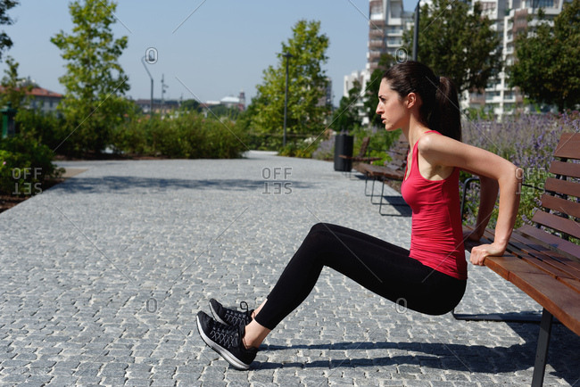 Young woman outdoors, doing push-ups on bench
