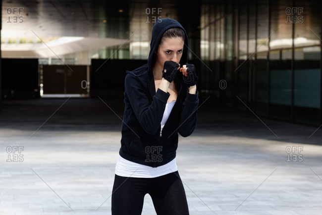 Young woman outdoors, exercising, in fighting stance