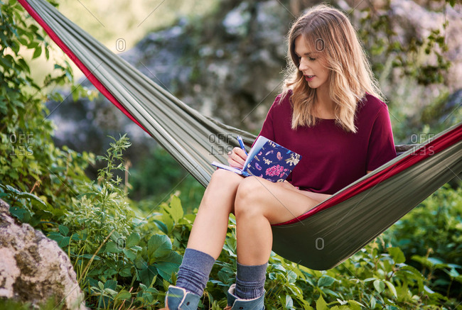 Woman sitting in hammock writing in notebook, Krakow, Malopolskie, Poland, Europe