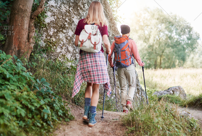 Rear view of couple with walking poles hiking in forest, Krakow, Malopolskie, Poland, Europe