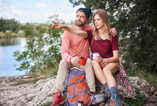 Couple hiking, sitting on rocks holding enamel mugs, Krakow, Malopolskie, Poland, Europe
