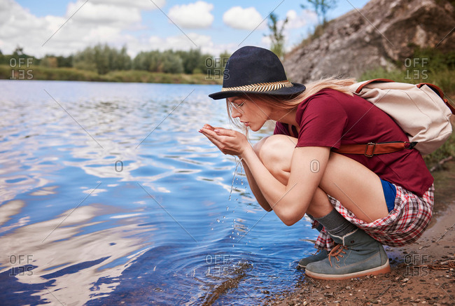 Woman crouching by waters edge scooping up water in hands, Krakow, Malopolskie, Poland, Europe