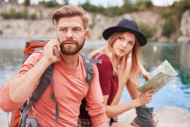 Couple with map using cellular phone, Krakow, Malopolskie, Poland, Europe