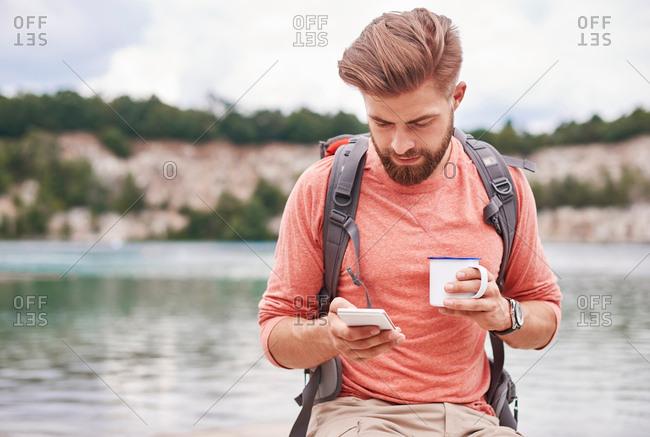 Man holding enamel mug using cellular phone, Krakow, Malopolskie, Poland, Europe