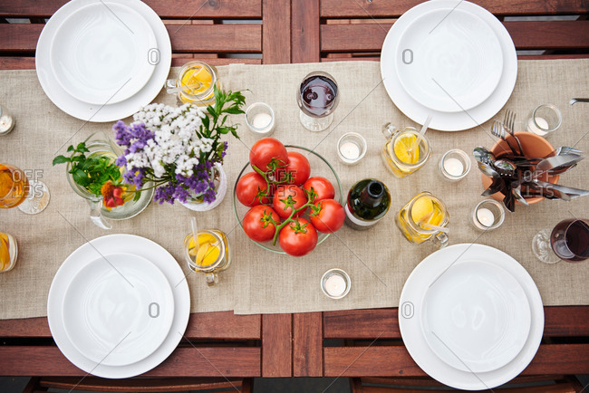 Overhead view of table prepared with flowers and vine tomatoes for lunch on patio