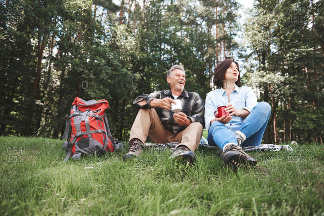 Mature couple relaxing on grass, holding tin cups, rucksack beside them