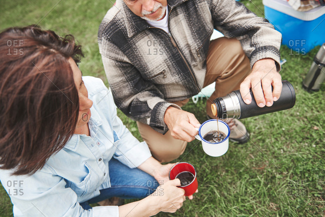 Mature couple crouching on grass, man pouring hot drink from drinks flask, elevated view