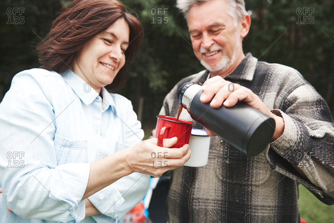 Mature couple outdoors, man pouring hot drink from drinks flask