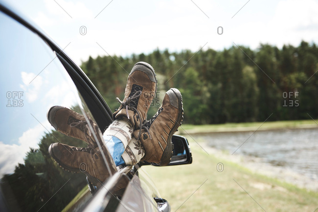 Woman relaxing in car, feet through open window, focus on feet