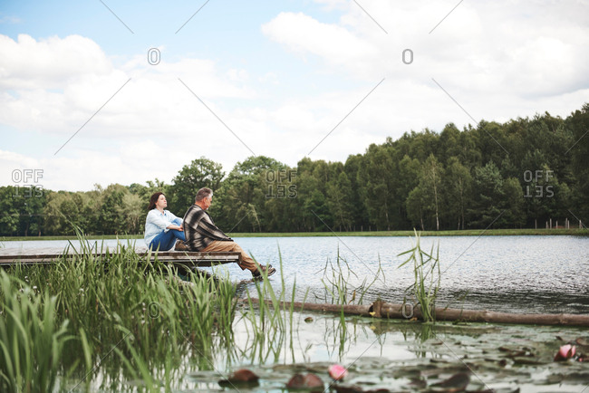 Mature couple relaxing on jetty beside lake