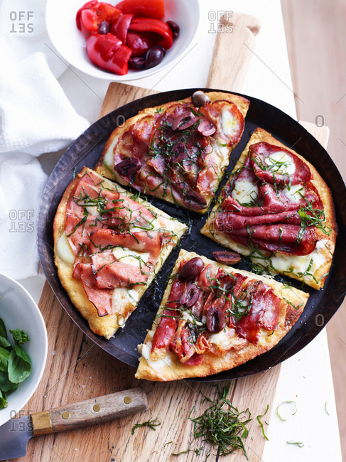 Sliced meat pizza in pizza dish, overhead view
