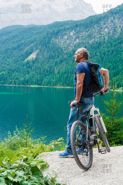 Senior man, standing, leaning on bicycle, looking at view, Elbsee, Bavaria, Germany