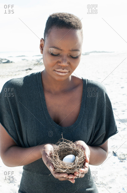 Portrait off young woman on beach, holding birds nest with egg in inside