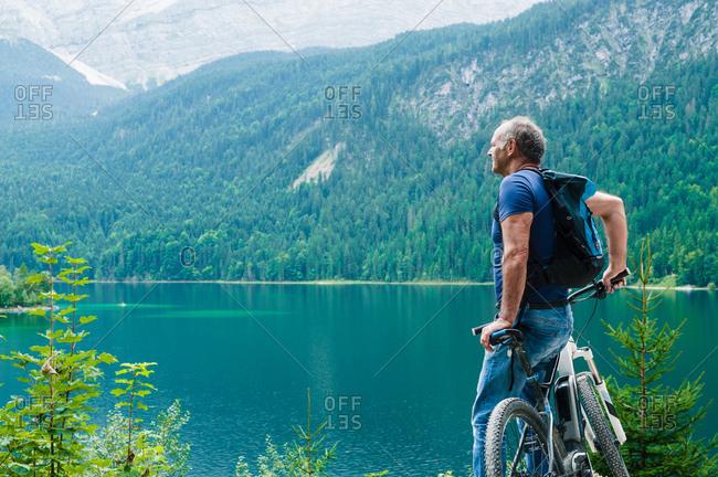 Senior man, leaning on bicycle, looking at view, Elbsee, Bavaria, Germany