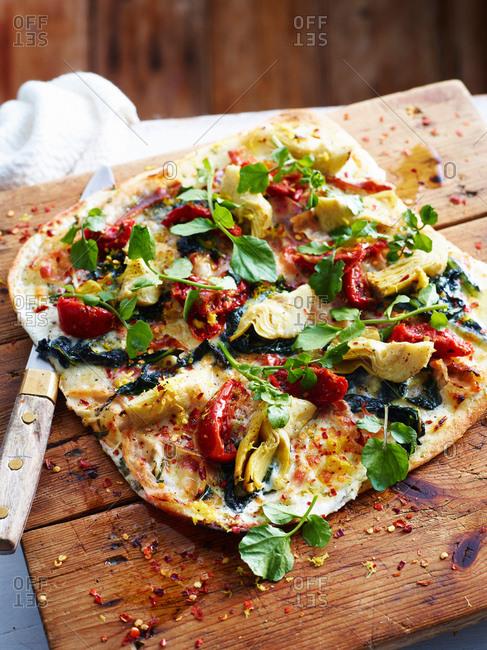 Pancetta, artichoke and chicory pizza on serving board, close-up