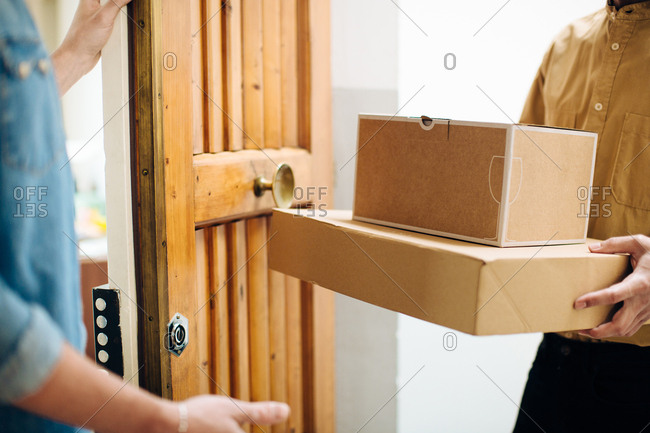 Man opening door to courier delivering parcels