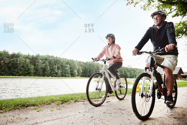 Mature couple cycling beside lake