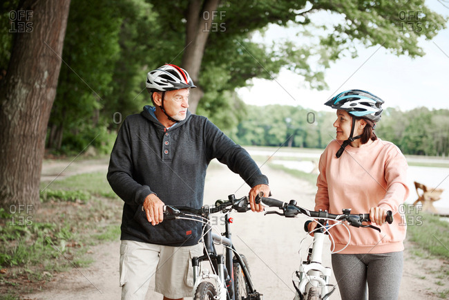 Mature couple walking along rural pathway with bicycles