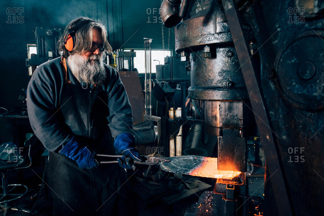 Blacksmith using blacksmith tongs for red hot metal in furnace