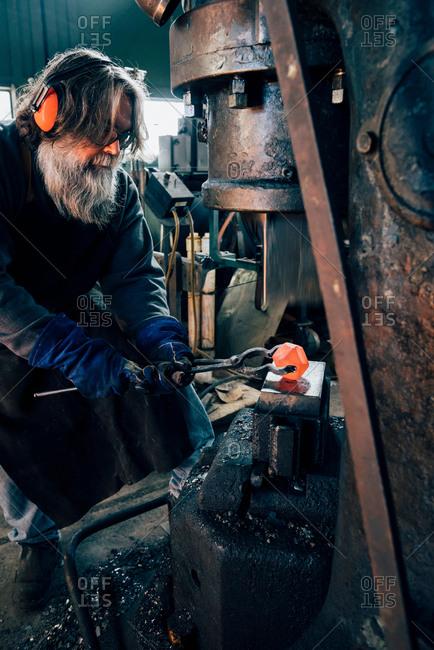 Blacksmith using blacksmith tongs for red hot metal