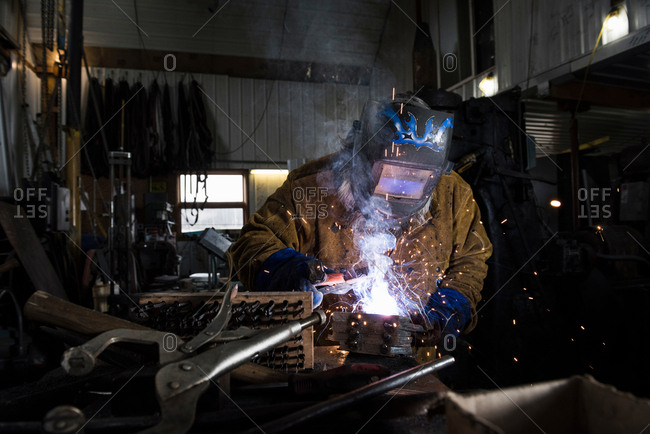 Blacksmith in welding mask welding metal in workshop
