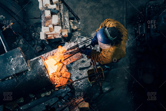 Overhead view of blacksmith shaping red hot metal rod in workshop furnace