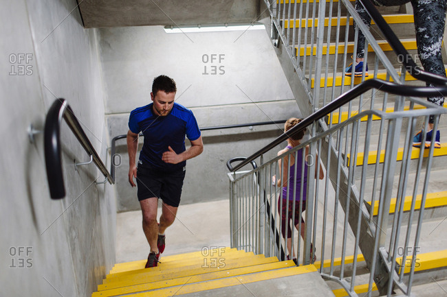 Young male runner running up indoor stairway