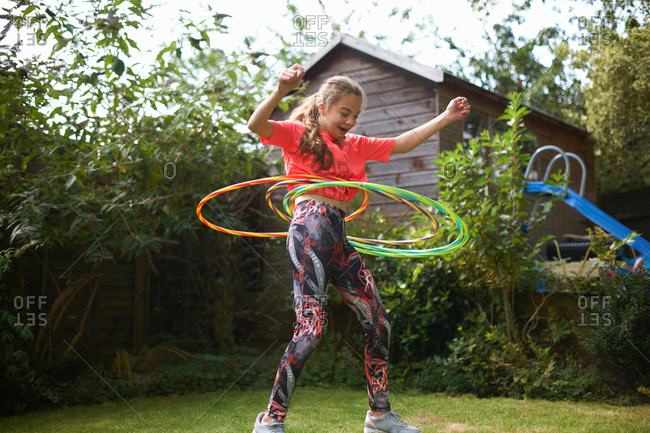 Teenage girl hula hooping with four plastic hoops in garden