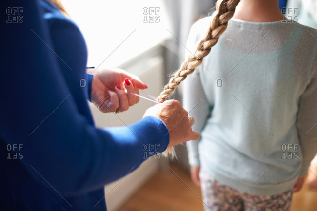 Cropped view of mother plaiting schoolgirl daughter's hair