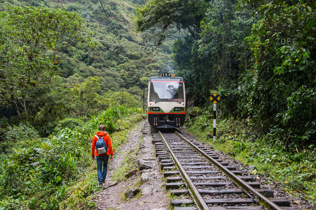 Male hiker hiking by train tracks that lead up to Aguas Calientesthe starting point for excursions to Machu Picchu, Peru