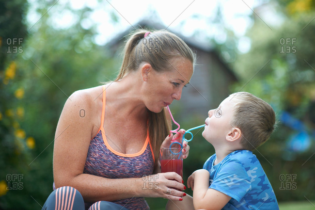 Boy and mother sharing fresh smoothie in garden
