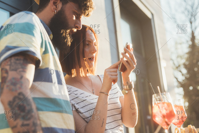 Couple using smartphone touchscreen at sidewalk cafe