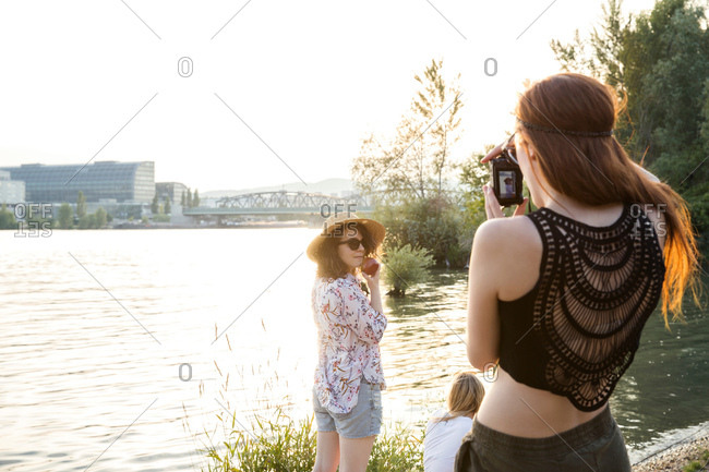 Three female friends at water's edge, young woman photographing friends