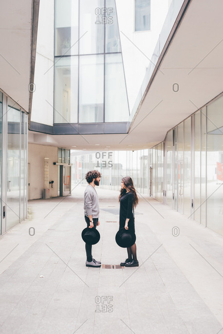 Young man and woman standing face to face in urban environment